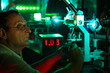 Scientist with glass demonstrate laser of microparticles