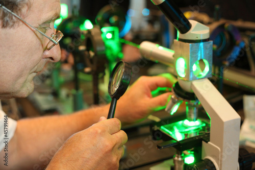 Scientist with glass, loupe configure laser of microparticles