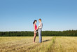 Husband hold hands wife and look on she in field, side