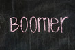 The word BOOMER handwritten with chalk  on a blackboard