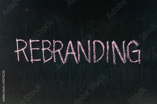 The word REBRANDING handwritten with chalk  on a blackboard