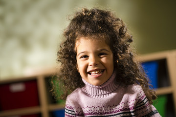 Happy child smiling for joy at camera in kindergarten