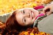junge Frau liegt im Laub
