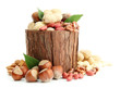 assortment of tasty nuts with leaves in wooden vase, isolated