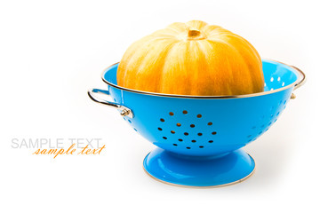 Pumpkin in blue colander on white background