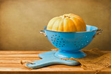 Pumpkin in blue colander on wooden tabletop against grunge wall poster