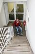Rollstuhlfahrer im Treppenhaus