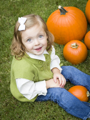 Cure Young Child Girl Enjoying the Pumpkin Patch.