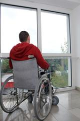 Rollstuhlfahrer vor Fenster