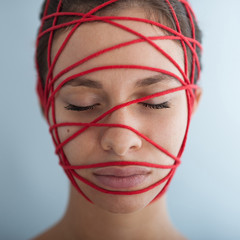 Close up of woman constrained with red ropes. Conceptual image.