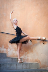 Young beautiful ballerina dancing on the stairs.