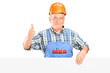 A male construction worker holding a panel and giving thumb up
