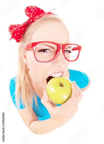 Funny  girl biting an apple isolated on white, fish eye shot