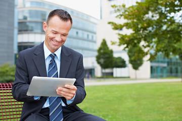 Geschäftsmann mit Tablet PC im Park