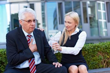 Frau bietet Senior mit Schmerzen Wasser an
