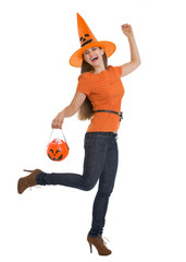 Full length portrait of happy woman holding Halloween bucket