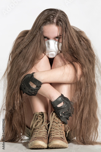 The girl with long hair sits in a mask