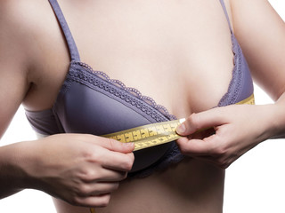 Young woman measures her Breast size - isolated