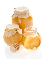 glass jar full of honey and stick on white