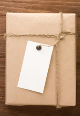 paper parcel wrapped tied with price tag on wood