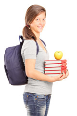 A smiling schoolgirl holding books and green apple