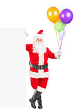 Santa claus standing next to a billboard and holding balloons