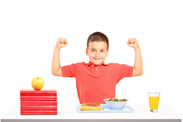 Strong boy showing his muscles and food on table during a breakf