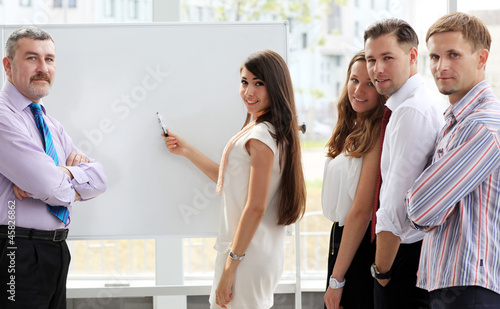 Business people looking at their leader while she explaining