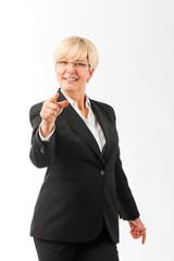 Ältere Frau zeigt mit dem Finger auf den Betrachter