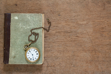 Antique book and old pocket watch on wooden background