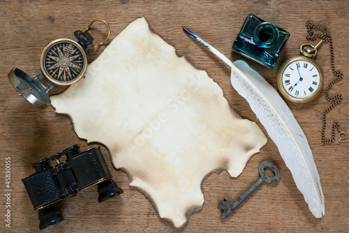 Compass, pocket watch, quill, inkwell, paper, binoculars on wood