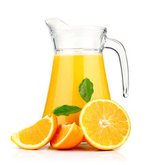 Orange juice in pitcher and oranges.
