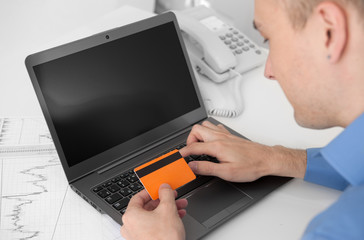 man shopping online with credit card and computer