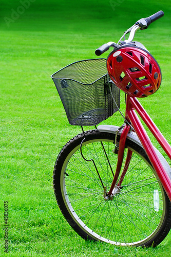 Red bike and a helmet on green grass