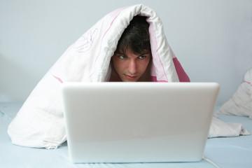 junger mann mit laptop im bett