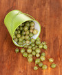 Green gooseberry in metal bucket on wooden background
