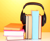 Headphones on books on orange background