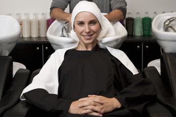 A female client sitting at a wash basin in a hairdressing salon