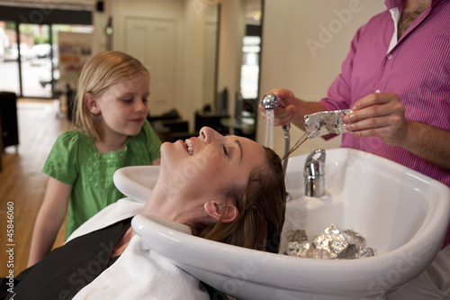 Girl watching mum have foils removed from hair in a hairdressers