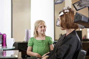 Mother has her hair coloured watched by young daughter