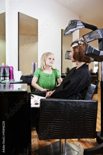 Mother has hair coloured watched by young daughter