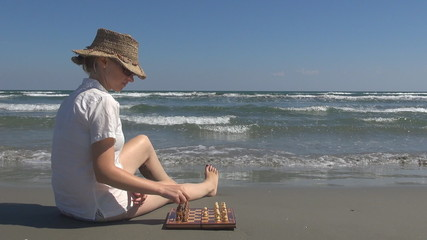 Beautiful woman playing chess on the beach