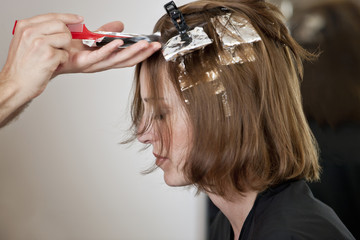 A woman having her hair coloured in a hairdressers, close up