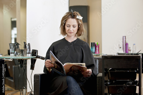 female client reading a magazine while she has her hair colored