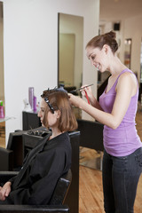 A female hairdresser colouring a female clients hair
