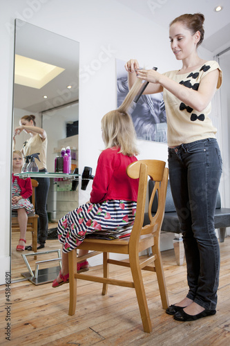 A female hairdresser cutting a young girls hair