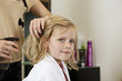 A female hairdresser spraying a young girls hair, close up