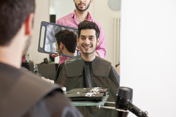 A male hairdresser showing his client his new haircut