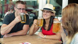 Young happy friends raising a toast with beer in bar