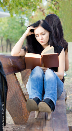 Girl reading a book on a bench
